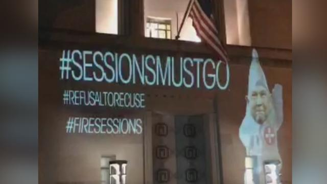 Artist Robin Bell projected an image of Attorney General Jeff Sessions dressed in KKK robes on the Department of Justice and FBI buildings in Washington. Bell called for Sessions' ouster.