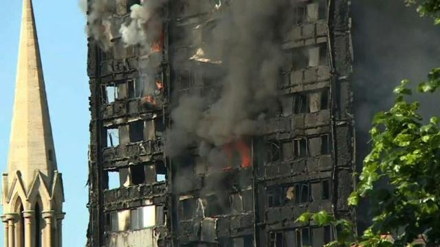 London fire: debris continues to fall from burning tower block